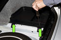 Disengage the battery trim cover by twisting the clips 90° counter-clockwise.