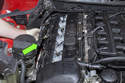 Unclip ignition coil wiring harness from valve cover by pulling up and remove from engine (green arrow).