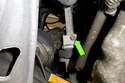 Working at the top of the power steering rack, remove E10 steering coupler fastener (green arrow).