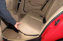 Working in rear of vehicle interior, grab corner of rear seat cushion and pull up to detach locking tabs.