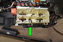 Working under passenger side of dashboard, remove relay 10mm panel support fastener (green arrow).