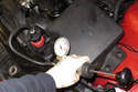 Working with a cold engine, install pressure tester to coolant expansion tank.