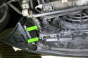 Working at lower left side of radiator, remove radiator and coolant expansion tank drain plugs (green arrows).