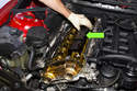 Remove plastic camshaft cover from cylinder head by pulling up and off cylinder head.