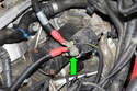 Working at the back of starter, remove the 13mm battery positive (+) cable nut (green arrow).