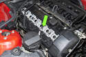 Working at the center of valve cover, remove the 8mm nut and ground strap from the valve cover fastener (green arrow).