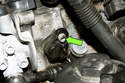 Next, remove the intake camshaft sensor using a 5mm Allen bit fastener (green arrow).