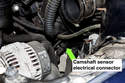 The camshaft sensor electrical connector is located below the throttle and behind the alternator.