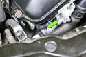 The BMW E46 camshaft sensor is located at the right front of your cylinder head - disconnect the camshaft sensor electrical connector (green arrow).