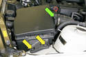Remove the air filter housing assembly fasteners (yellow arrows) and disconnect the air flow meter electrical connector (green arrow).