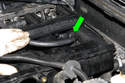 Now, on top of the intake manifold, unclip the battery positive (+) cable from the intake manifold (green arrow).