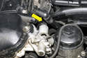 At the intake VANOS solenoid, disconnect the VANOS solenoid electrical connector by releasing the tab and it pulling off (yellow arrow).