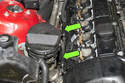 Locate the oxygen sensor electrical connectors at the right side of engine above exhaust manifold (green arrows).