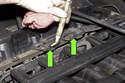 Locate the oxygen sensor electrical connectors on top of the engine near the fuel rail (green arrows).