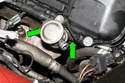 Next, remove the two 10mm secondary air valve fasteners (green arrows).