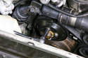 Before removing your engine drive belt, loosen four 10mm water pump pulley fasteners but do not remove them completely (green arrows).