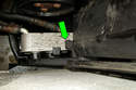 Working at lower right side of the coolant expansion tank, locate the coolant expansion tank release tab (green arrow).