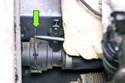 Next, using a flathead screwdriver, release the lower radiator hose retaining clip by prying it up (green arrow).