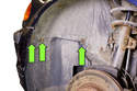 While, working inside the front wheel well, remove the three splash shield screws (green arrows).