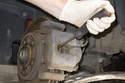 Using a flathead screwdriver, slowly press the brake caliper piston in.