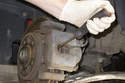 Using a flathead screwdriver, slowly push the brake caliper piston in.