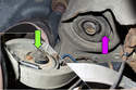 Inspect upper (purple arrow) and lower (green arrow) spring pads for wear or damage.
