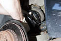 With both spring pads installed on new spring, install the spring into the vehicle, top of the spring first.