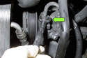 Now, working from under your vehicle at the front corner, using a 17 mm wrench, remove the power steering pump high pressure line (green arrow).