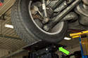 Next place the hydraulic jack under the trailing arm or under rear tire (green arrow).