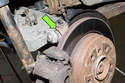 This photo shows the rear ball joint (green arrow) connecting the rear upper control arm to the rear wheel bearing carrier.