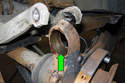 Once the ball joint has been removed, clean the mounting area of rust and debris (green arrow).