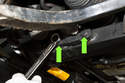 Next, working at subframe, loosen the two inner ball joint 18mm mounting fasteners (green arrow).