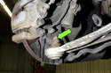 Working at the steering knuckle, remove the 16mm ball joint nut (green arrow).