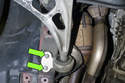 Working at the rear of front control arm, remove the two 16mm control arm bushing fasteners (green arrows).