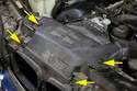 Working at the top of the radiator, remove the expansion rivets from the intake air duct (yellow arrows).