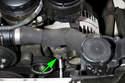 Working at the bottom of the alternator, loosen lower alternator mounting bolt (green arrow).