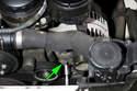 Working at the bottom of the alternator, loosen lower alternator mounting bolt (green arrow).