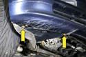 Работая из-под автомобиля, снимите винты с левого и правого нижних углов переднего бампера, по два с каждой стороны (желтые стрелки).
