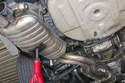 Support the exhaust system from below using a hydraulic floor jack or jack stand.