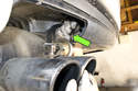 If your vehicle has a tailpipe flap, disconnect the vacuum hose to tailpipe flap (green arrow).