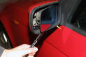 Using a plastic prying tool, gently lever out the mirror glass.