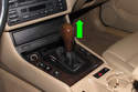 Next, remove the shift knob by pulling it straight up and off the shift lever (green arrow).