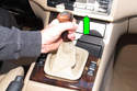 Next, remove the shift knob by it pulling straight up and off the shift lever (green arrow).