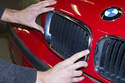 Install the new grilles by feeding them into engine hood and pressing around chrome grille edges.
