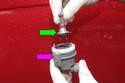 Pull the headlight bulb (green arrow) out of the bulb holder (purple arrow).
