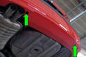 Working under the center of the bumper, locate the two bumper bolt access holes (green arrows).