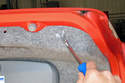Pry the center of rivet out using a trim panel tool and remove the rivet from the trim panel.