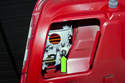 To replace the trunk mounted lens, remove the mounting fastener (green arrow).