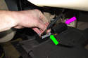 Lower trim panel, then remove OBD II connector by sliding locking tab and pulling out of trim panel (green arrow).