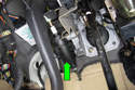 Working at clutch master cylinder (green arrow), remove two fasteners.